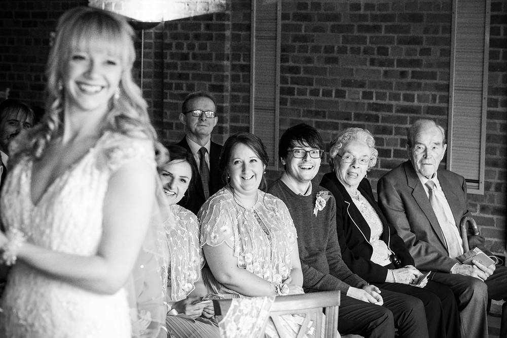 Smiling guests watching on during wedding ceremony at Birmingham museum