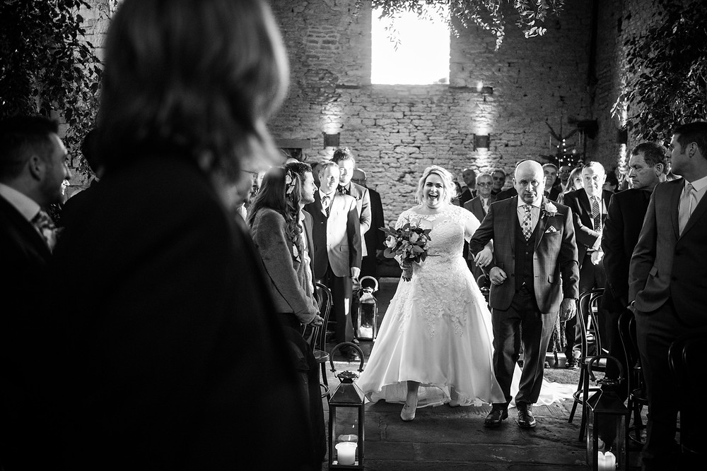 Bride laughing as she walks down the aisle at Cripps Barn for her winter wedding