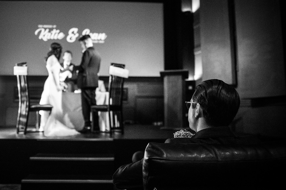 Black & White photograph of Best Man looking on as bride & groom get married at The Electric Cinema