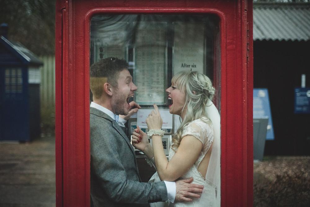 Laughing Bride & Groom in phonebox at Avoncroft Museum wedding