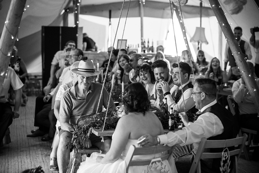 Documentary photograph of laughing guests during wedding speeches at Derbyshire Tipi wedding