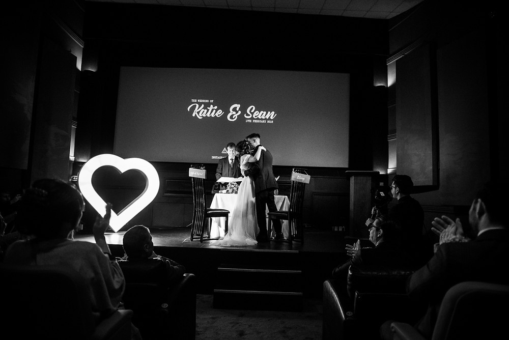 B&W image of bride and groom kissing at the end of their wedding ceremony at The Electric Cinema