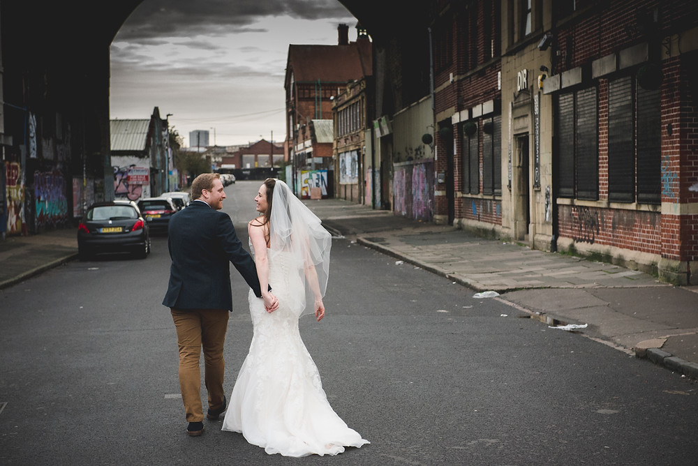 Bride & Groom walking off hand in hand in Digbeth after their wedding