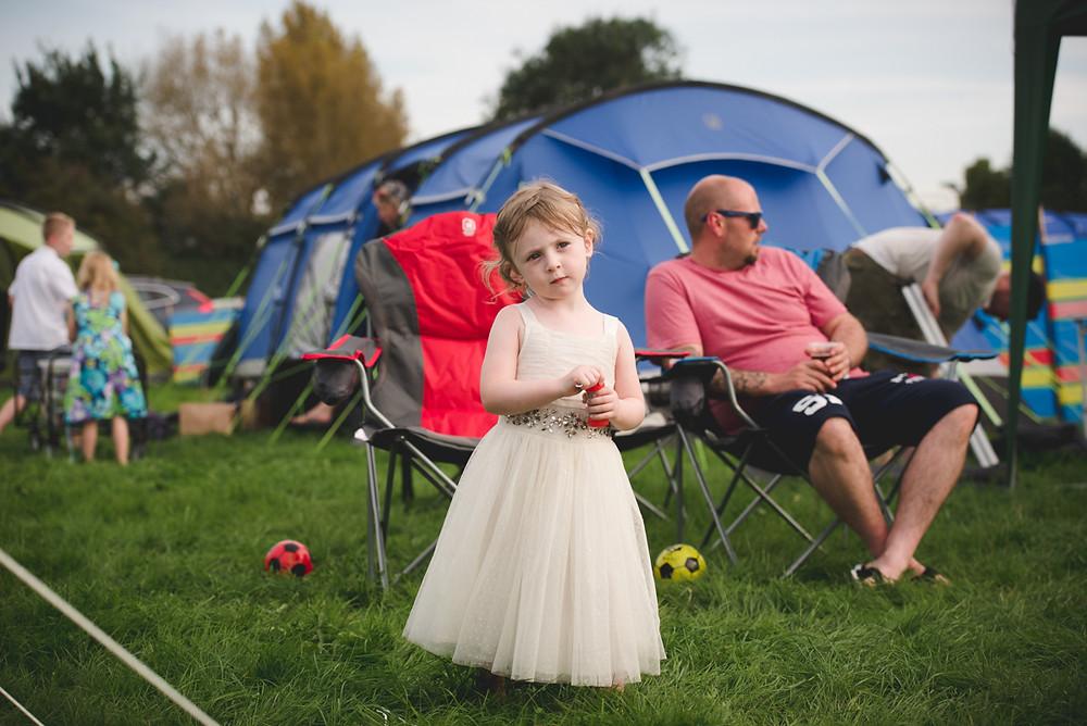 flowergirl in field at festival wedding