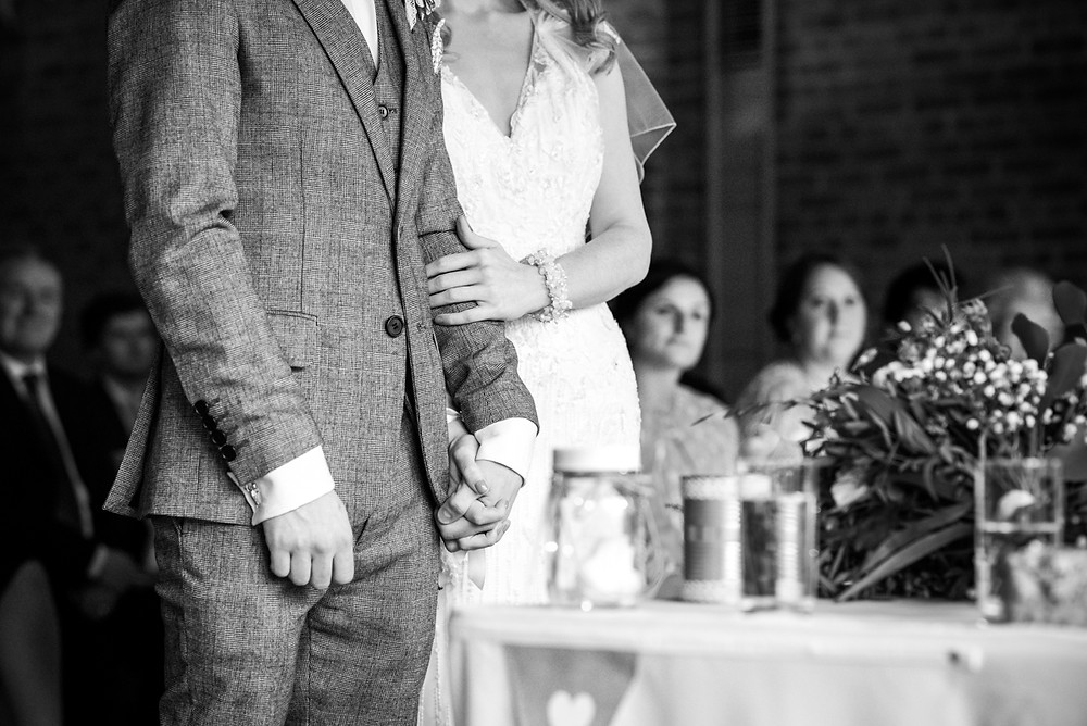 Bride holding the arm of her groom during relaxed wedding ceremony at Avoncroft Museum