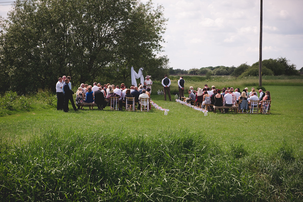 Wedding guests in a field next to river trent for open air wedding