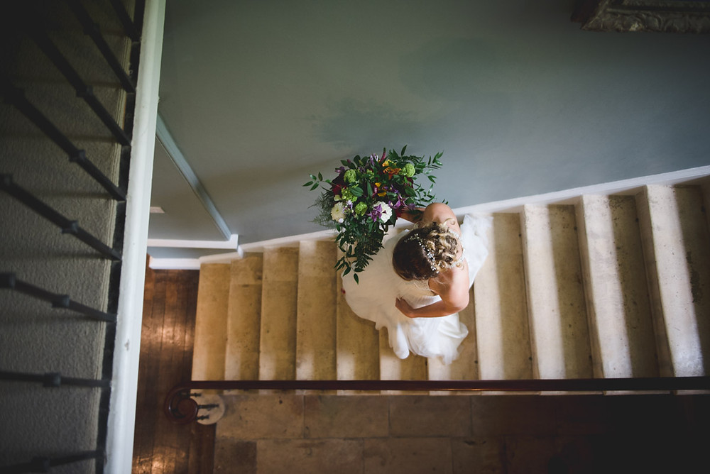 candid wedding photo of bride walking down the stairs at The Matara Centre