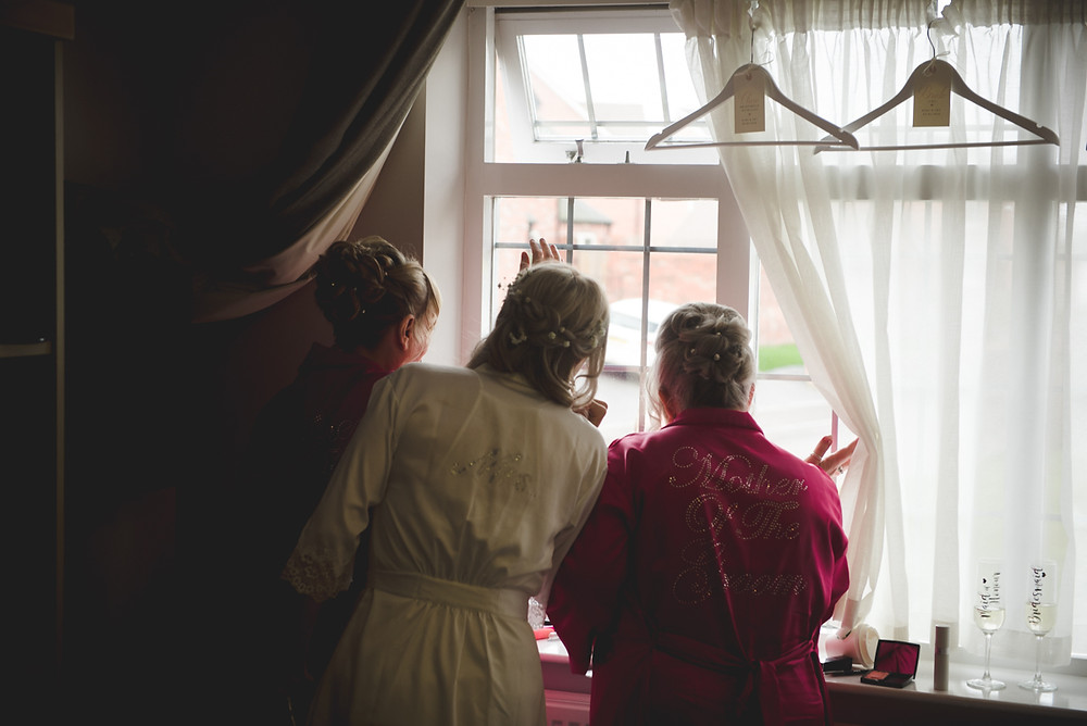 Bride and her mother looking out of the window getting ready before Avoncroft museum wedding