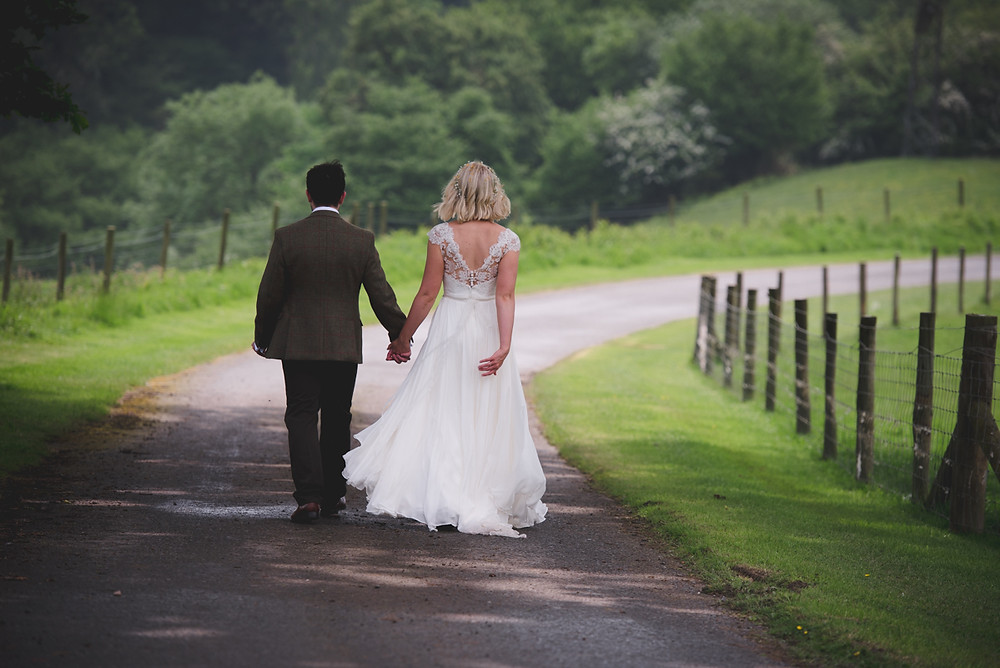 Relaxed wedding photograph as bride & groom walk down the lane at Ludlow wedding