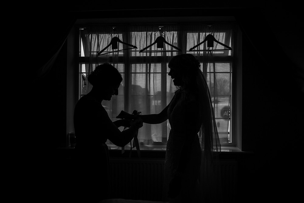 Silhouette of bride and bridesmaid getting ready for Avoncroft museum wedding