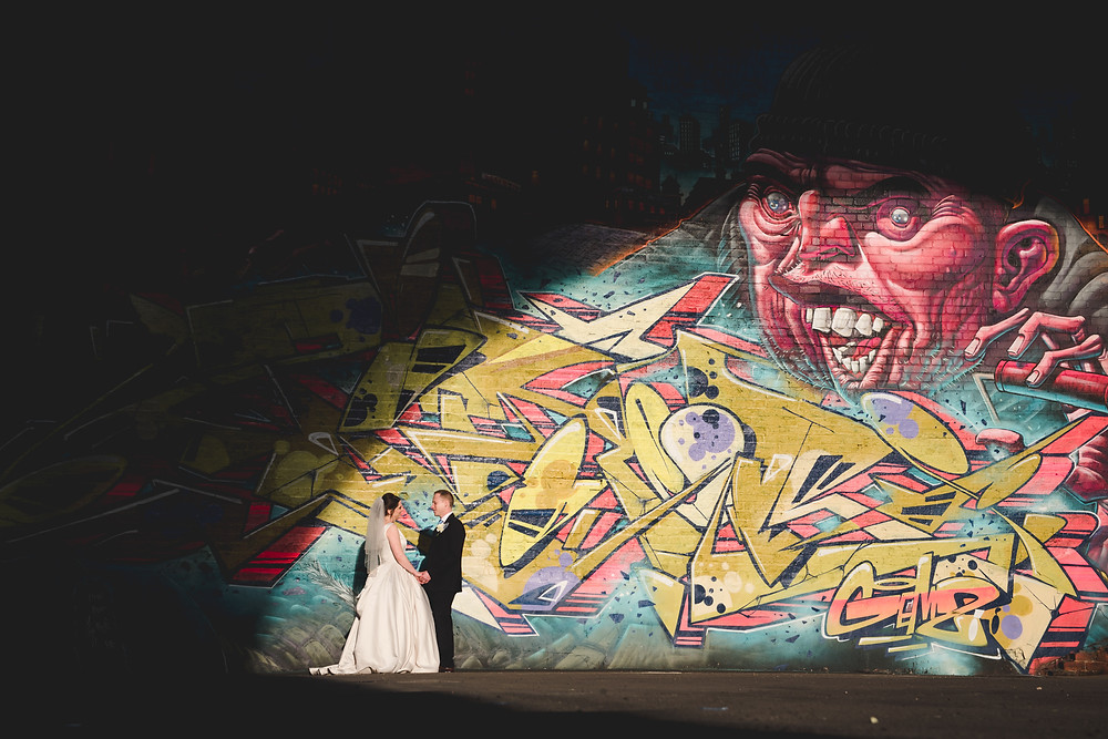 Digbeth graffiti in the background as newlyweds enjoy a moment after their Old Library Wedding