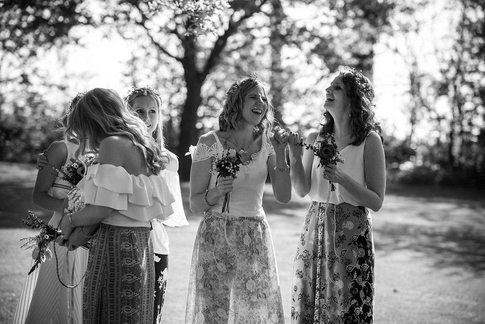 laughing bridesmaids during drinks reception at summer wedding in Warwickshire