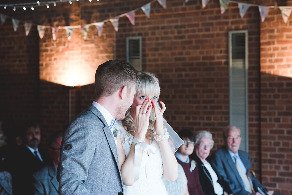 Bride wiping tears from her eyes during Birmingham wedding at Avoncroft Museum