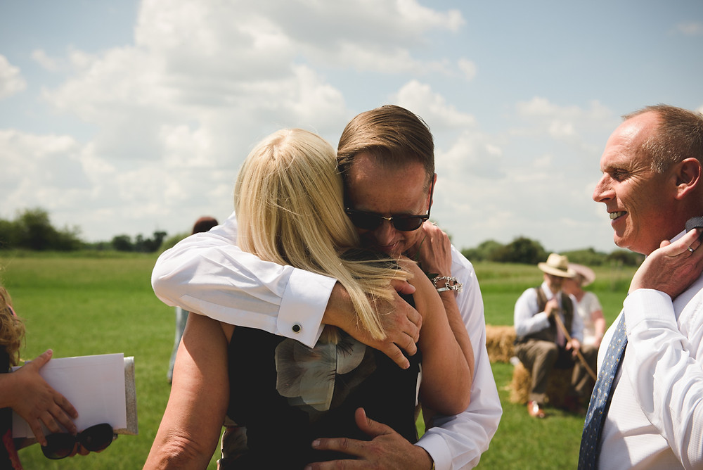 Groom embracing a guest before his outdoor wedding next to the river Trent in Derbyshire