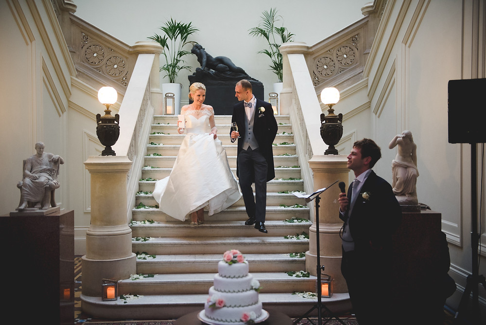 Bride & Groom walking down grand staircase for speeches at their Herefordshire wedding