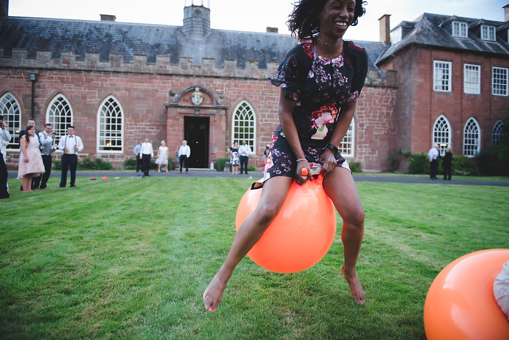 Wedding guests at Hartlebury Castle having space hopper race