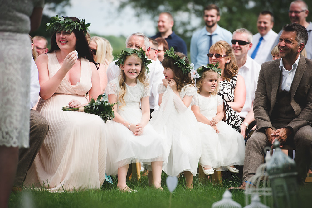 happy flower girls and bridesmaids sitting on wooden benches during open air wedding at Cuttlebrook Farm