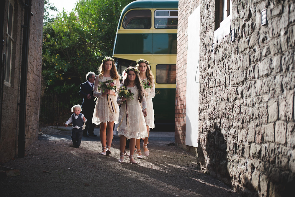 Flower girls walking from vintage bus at Lyde Court wedding in Herefordshire