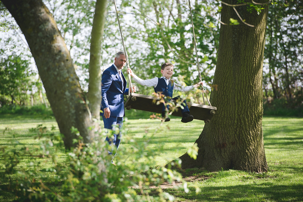 Smiling boy on swing at Wethele Manor Warwickshire wedding venue
