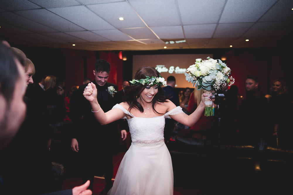 Happy bride raising her arms aloft in triumph after getting married at The Electric Cinema