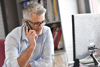 Businessman in office talking on phone .