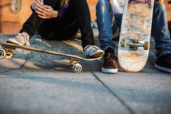 Group of Skaters siting on the sidewalk