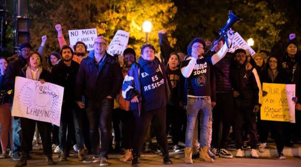 """Drake Materre and other student activists at 2017 Homecoming protest against the inclusion of racist """"chief"""" caricature in UIUC's parade"""