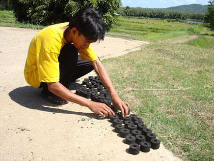 Training one of ULAN's partner-communities how to make charcoal briquettes from waste coco