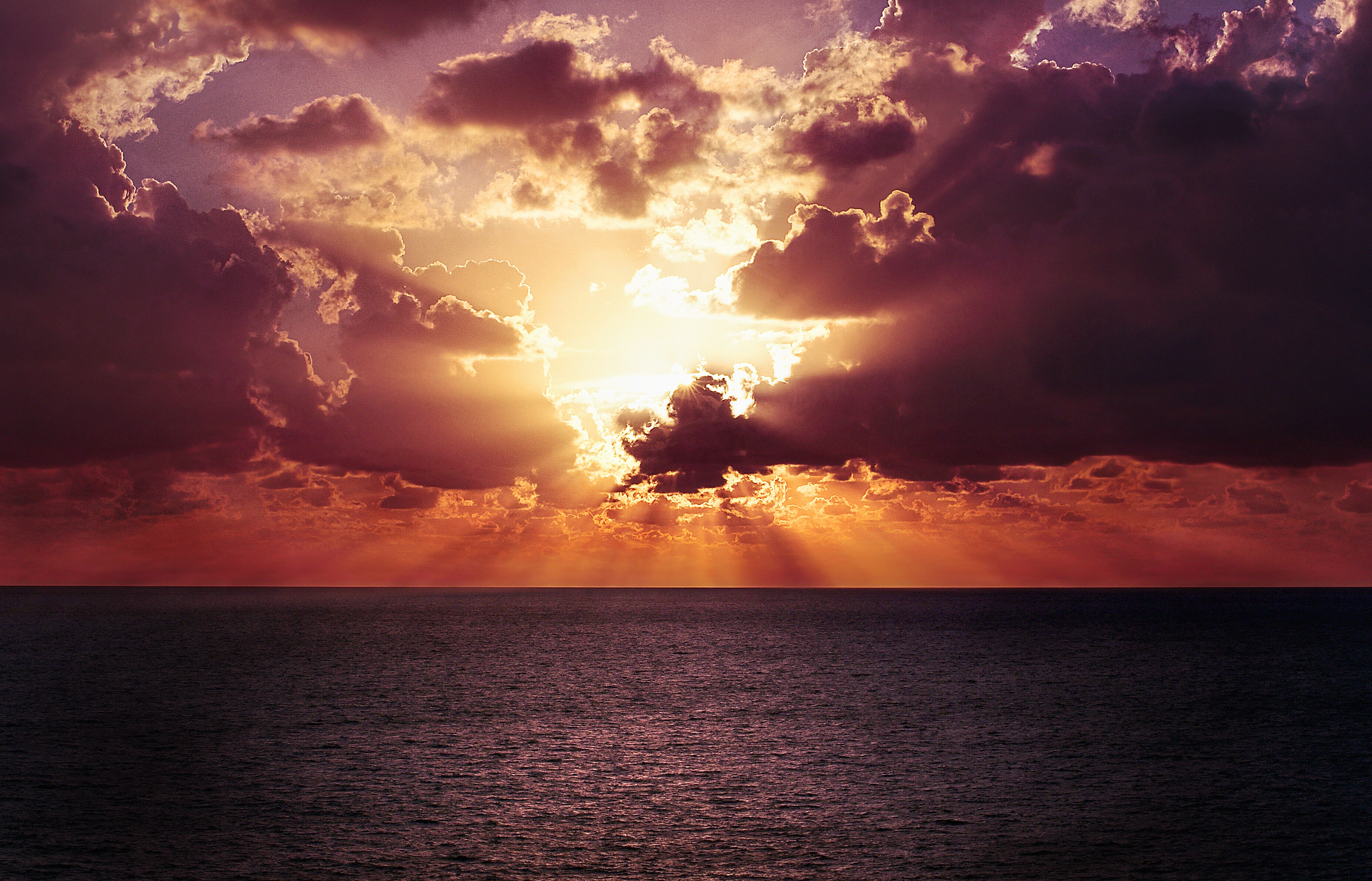 sun_rays_shining_through_clouds_during_calm_ocean_sunset_605721