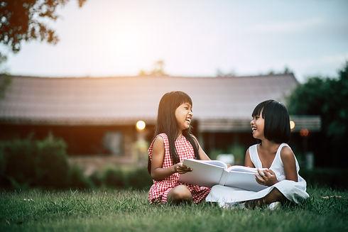 two-little-girl-friends-park-grass-readi