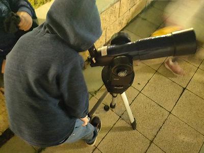 ילד צופה בטלסקופ בקורס אסטרונומיה באור י