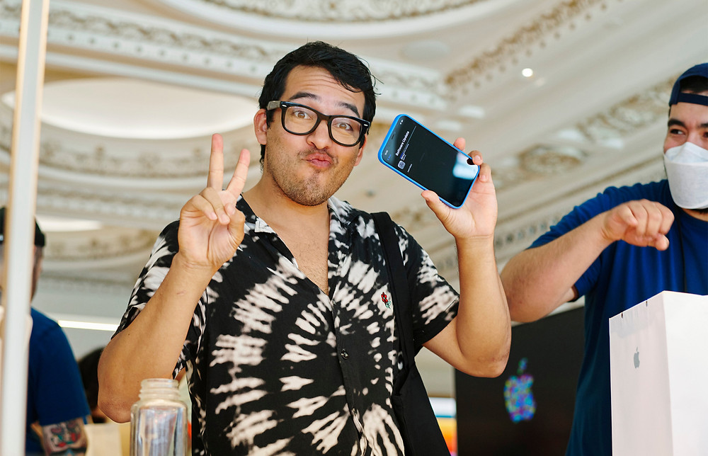A customer poses with his new iPhone in the opening of Apple's new store in LA