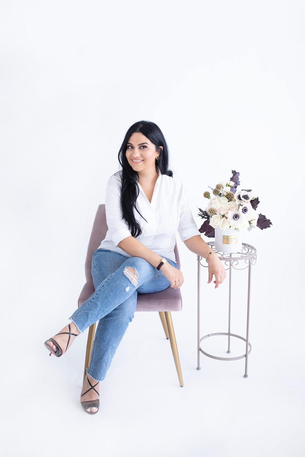 Women with long dark hair sitting down with jeans