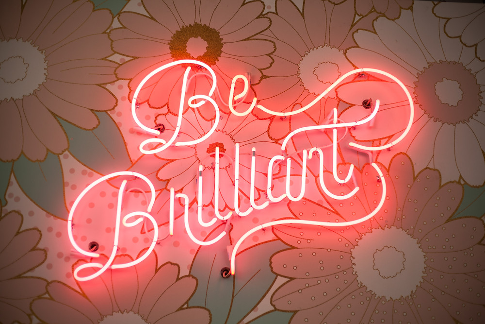 """Neon pink sign that says """"Be Brilliant"""""""