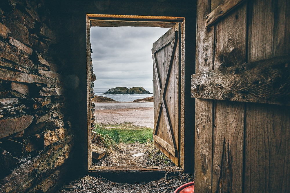 wooden alcove leading to a gray sky and beach