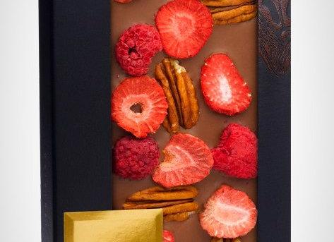 Молочный шоколад с орехами пекан, ломтиками клубники, ягодами малины