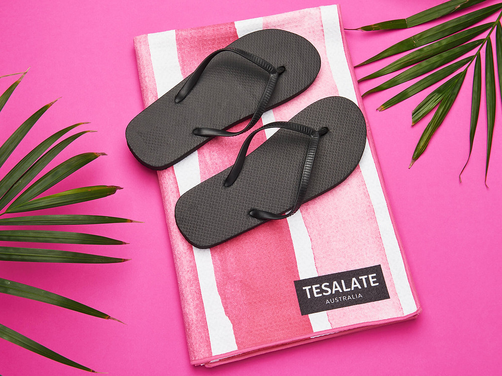 A pink striped Tesalate towel, black thongs and palm fronds on a bold pink background.