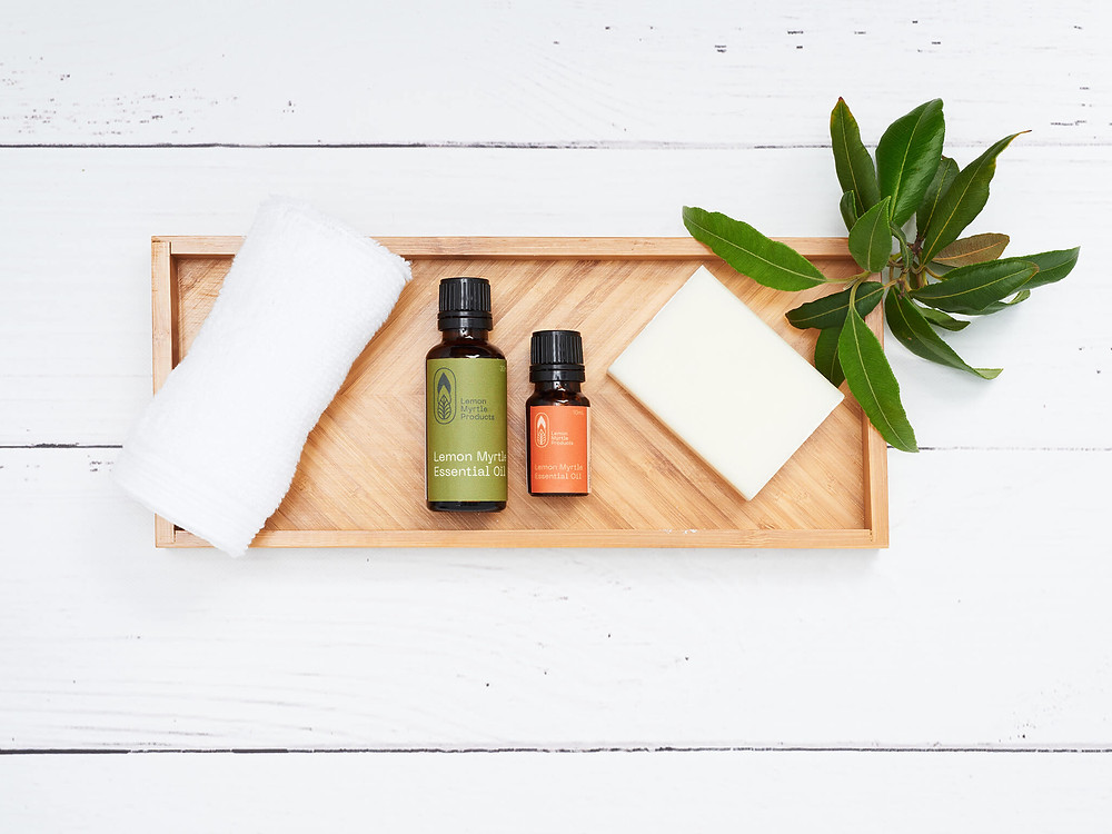 Green and orange bottles of essential oils work well against a timber tray, pure white face washers and a bunch of gum leaves.
