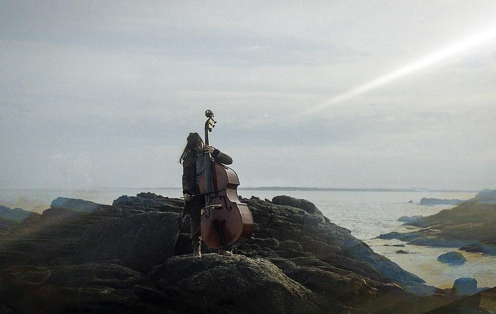Fernanda Pavanelli tocando violoncelo na praia uruguaia de José Ignacio em cena do filme brasileiro Verlust (2020), de Esmir Filho | Foto: Divulgação (Mostra Internacional de Cinema em São Paulo)