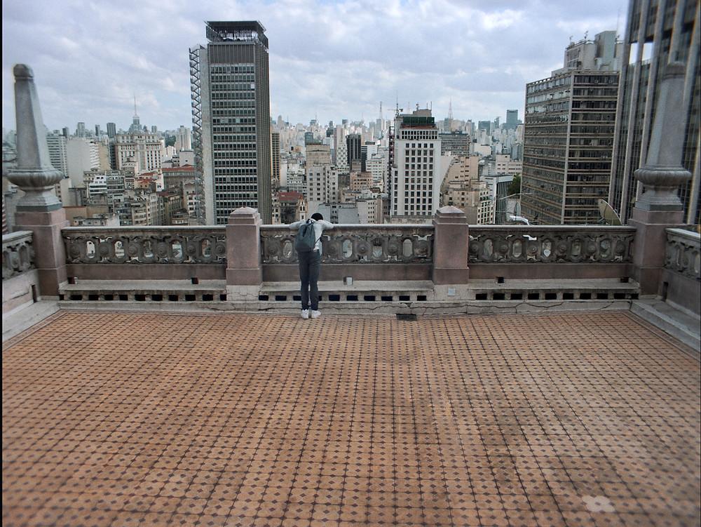 O ator nigeriano OC Ukeje do alto de um prédio na cidade de São Paulo, em cena do filme brasileiro Cidade Pássaro (2020), de Matias Mariani | Foto: Divulgação (Primo Filmes)