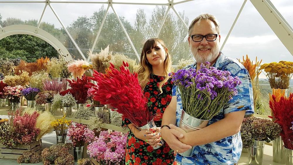 Natasia Demetriou e Vic Reeves, os apresentadores do reality show Batalha das Flores (2020), competição de jardinagem e paisagismo | Foto: Divulgação (Netflix)