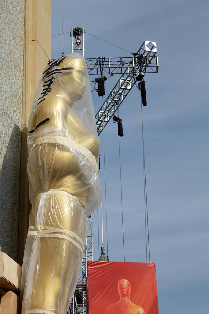 Estátuas do Oscar sendo levantadas durante a preparação da premiação da Academia em 2010 | Foto: Lisa Norman