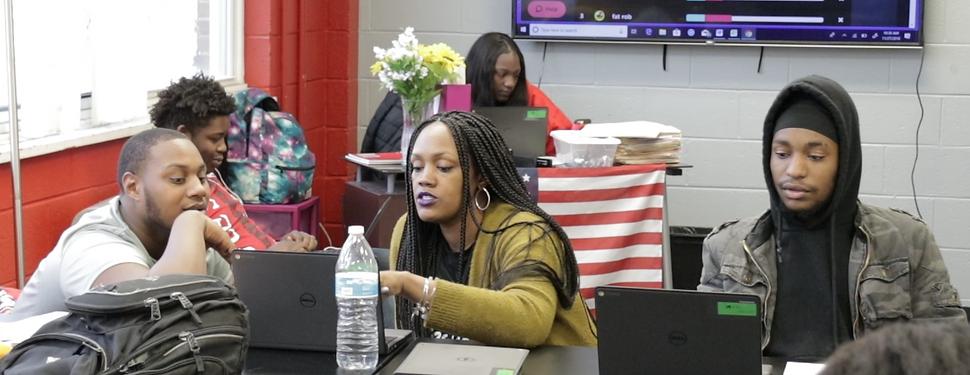 Four Kingsman students work on computers as their teacher helps them.