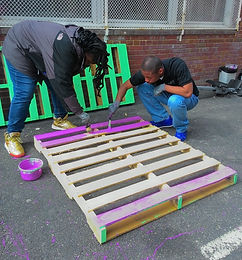Kingsman students paint wooden pallets behind the school