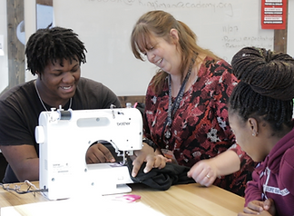 A Kingsman teacher helps a student use a sewing machine.