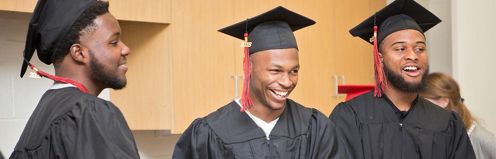 Three Kingsman graduates laugh together before the graduation ceremony.