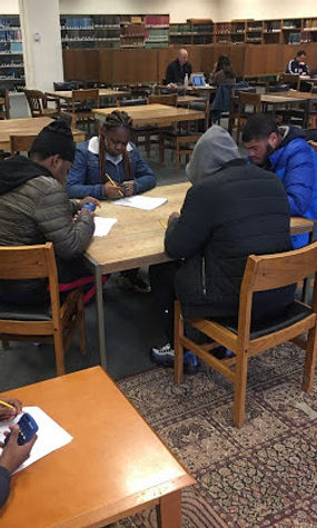 Five Kingsman student work in a library off-campus.