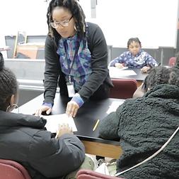 A Kingsman teacher provides personal suport during class
