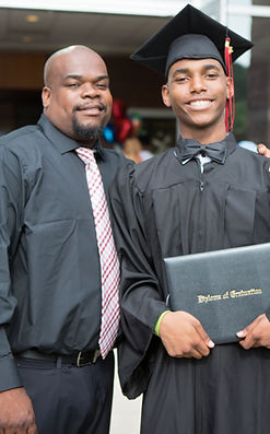 A Kingsman graduate and his teacher pose together at graduation.