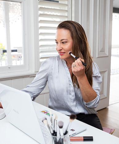 Woman doing an online makeup lesson at a laptop